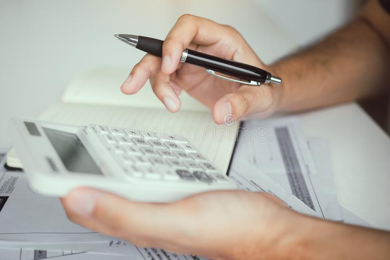 Man use calculators and documents that calculate expenses in the home office.  royalty free stock image