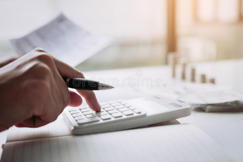 Man use calculators and documents that calculate expenses in the home office.  stock images