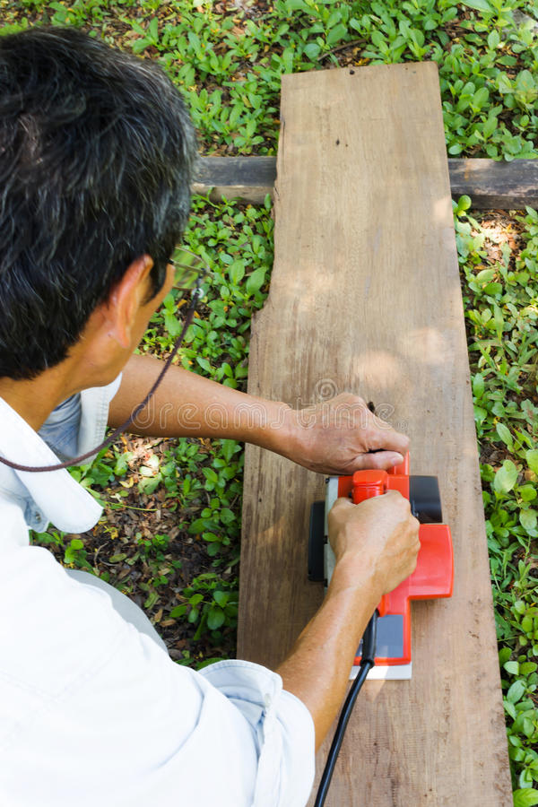 Man use electric wood plane. stock images