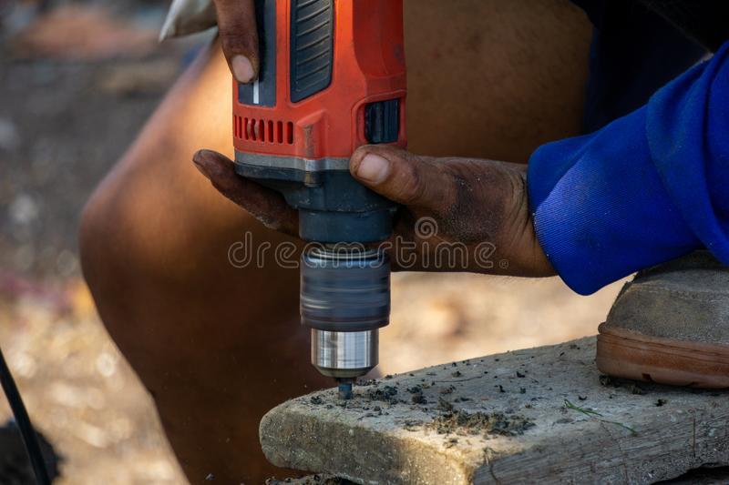 Man use electrical portable drilling machine to drill on an old wooden plank stock image
