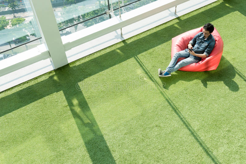 Man use smartphone on bean bag in afternoon, freelance conceptual lifestyle, internet in everyday life stock photography