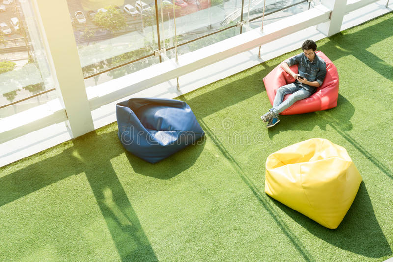 Man use smartphone on bean bag in afternoon, freelance conceptual lifestyle, internet in everyday life stock image
