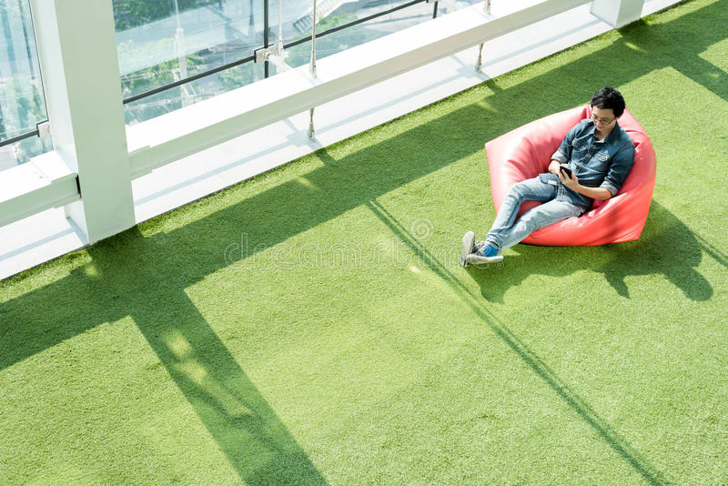 Man use smartphone on bean bag in afternoon, freelance conceptual lifestyle, internet in everyday life stock photos