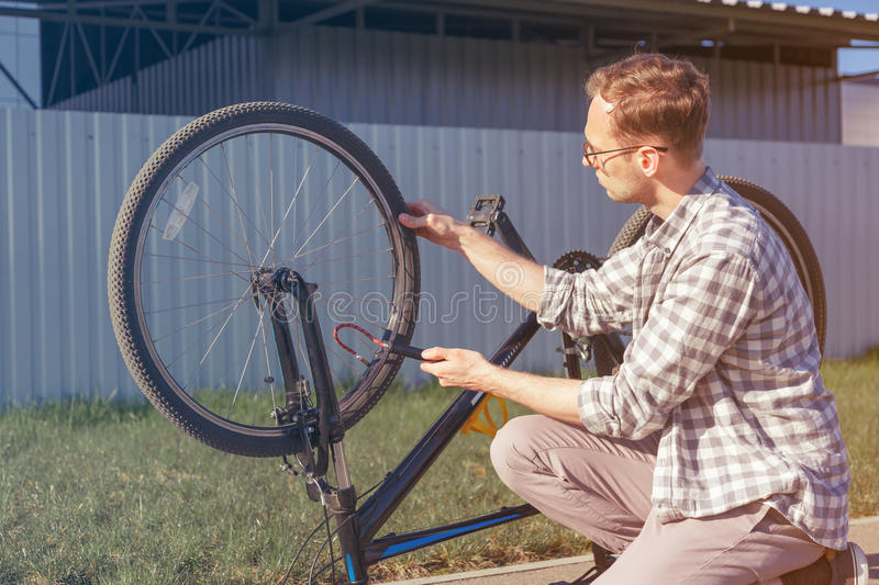 Man uses a bicycle pump. Cyclist repairs bike in trip. Man uses a bicycle pump. Inflating the tire of a bicycle. Cyclist repairs bike in trip stock images