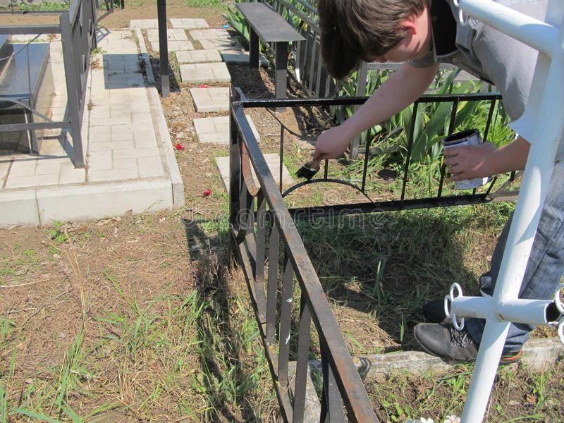 A man uses a brush to paint an iron fence with black color stock images