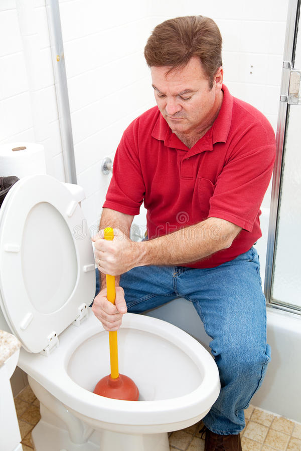 Man Uses Plunger on Clogged Toilet royalty free stock photos