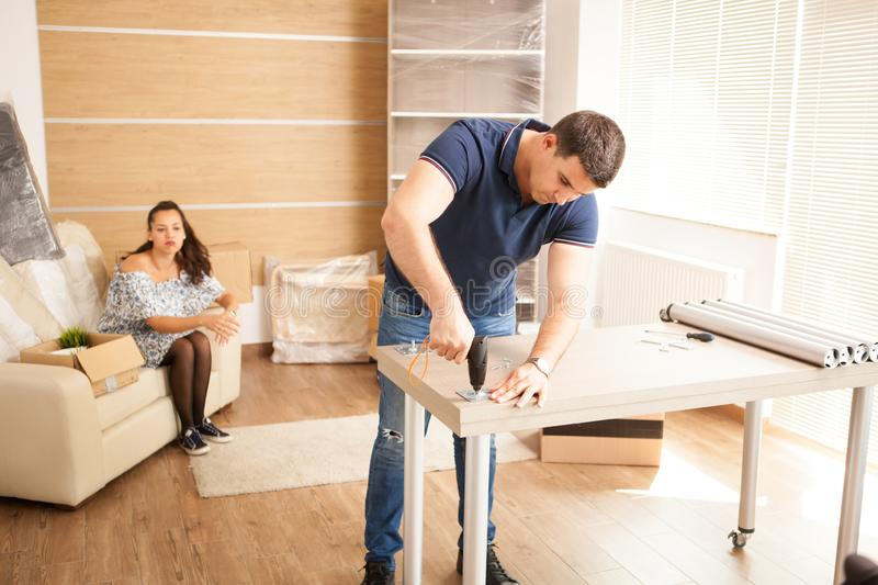 Man uses tools to assembly furniture in new house. He will use this furniture for the interior of the new flat stock images