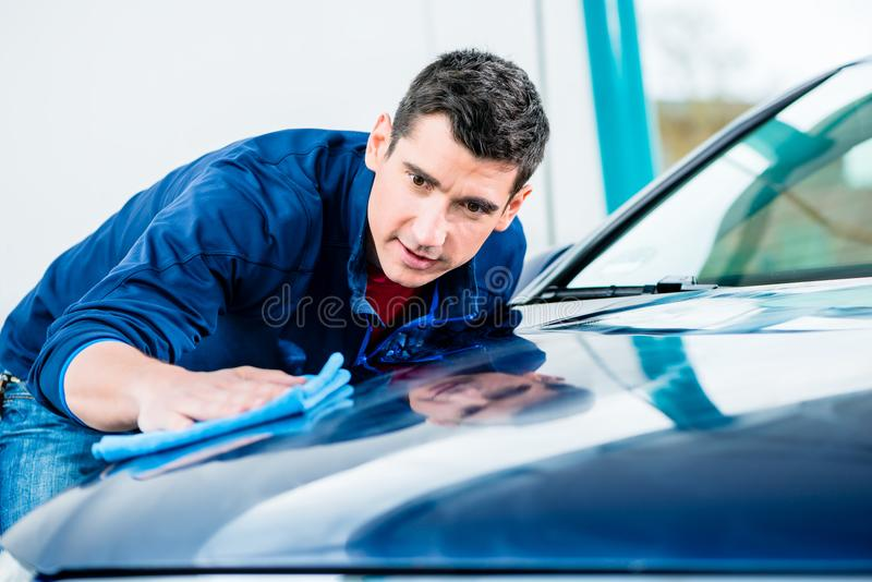 Man using an absorbent towel for drying the surface of a car. Young man using an absorbent soft towel for drying and polishing the surface of a clean blue car royalty free stock image