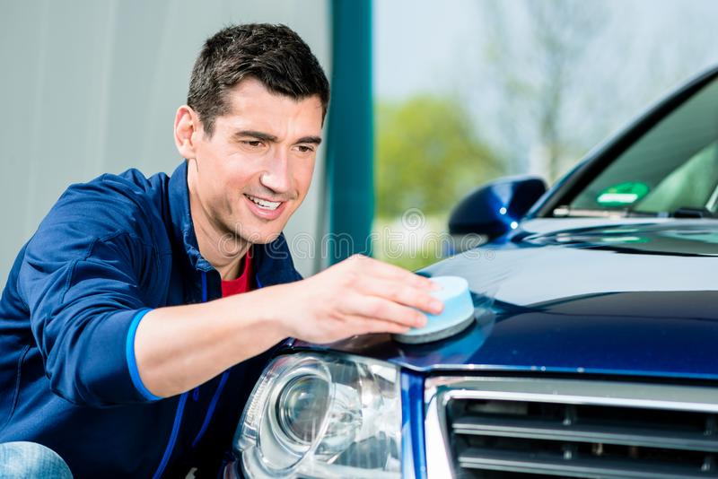 Man using an absorbent towel for drying the surface of a car. Young man using an absorbent soft towel for drying and polishing the surface of a clean blue car stock photo