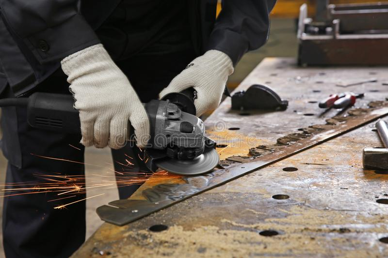Man using angle grinder for metalworking stock photography