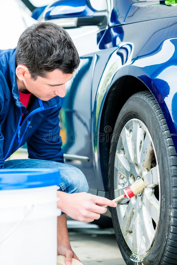 Man using brush for cleaning the surface of the rim. Young man using brush for cleaning the surface of the rim of a blue car at auto wash stock photos