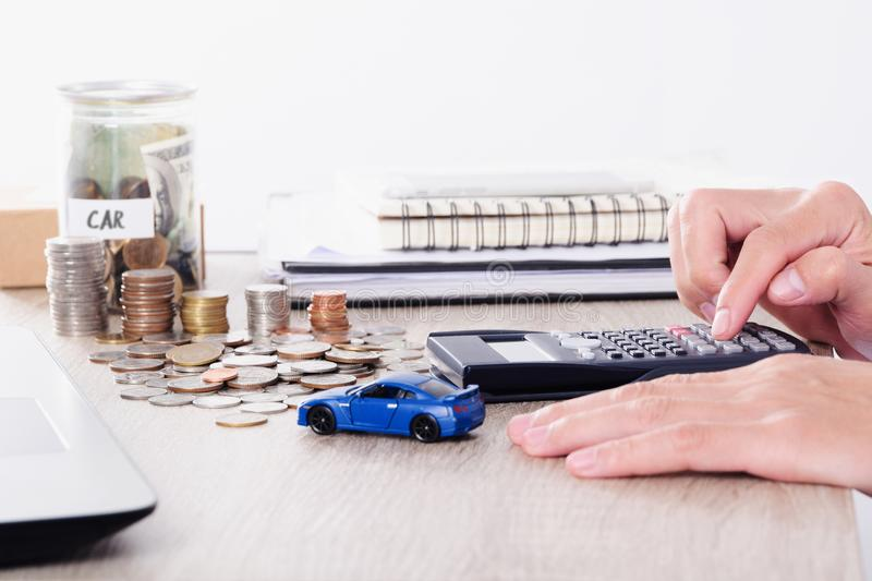 Man using calculator with car toy and coin stack for insurance loan or Saving for buying car concept.  royalty free stock image