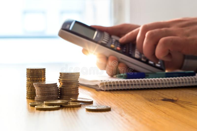 Man using calculator to count money savings and living costs. stock photos