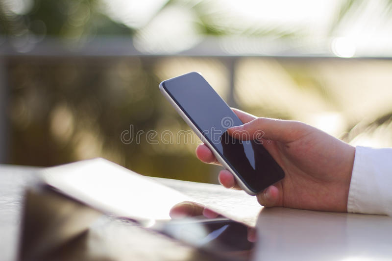 A man using a cell phone and digital tablet. Close up royalty free stock photo