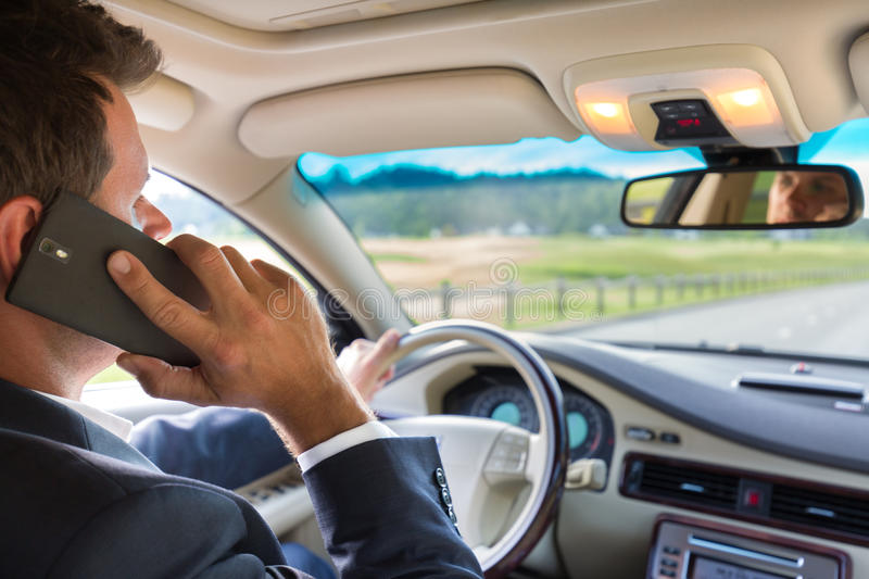 Man using cell phone while driving stock image