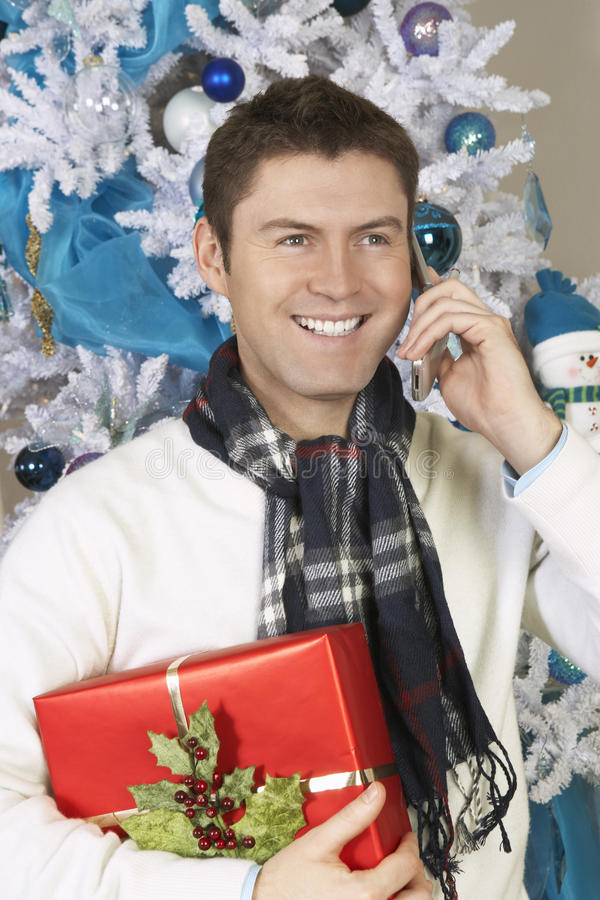 Man Using Cell Phone Holding Present By Christmas Tree stock image