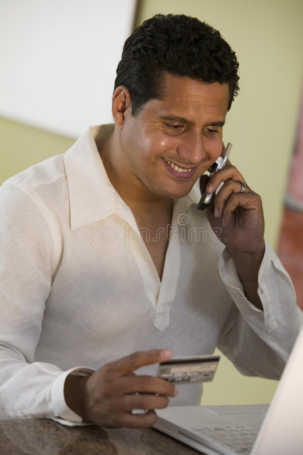 Man Using Cell Phone and laptop to purchase with credit card at home royalty free stock images