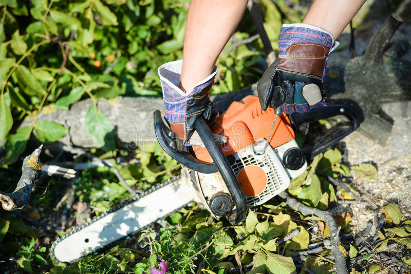 Man using chainsaw. closeup of his hands stock photos