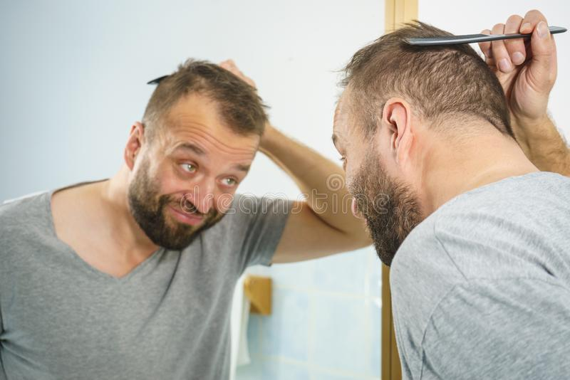 Man using comb in bathroom stock photography