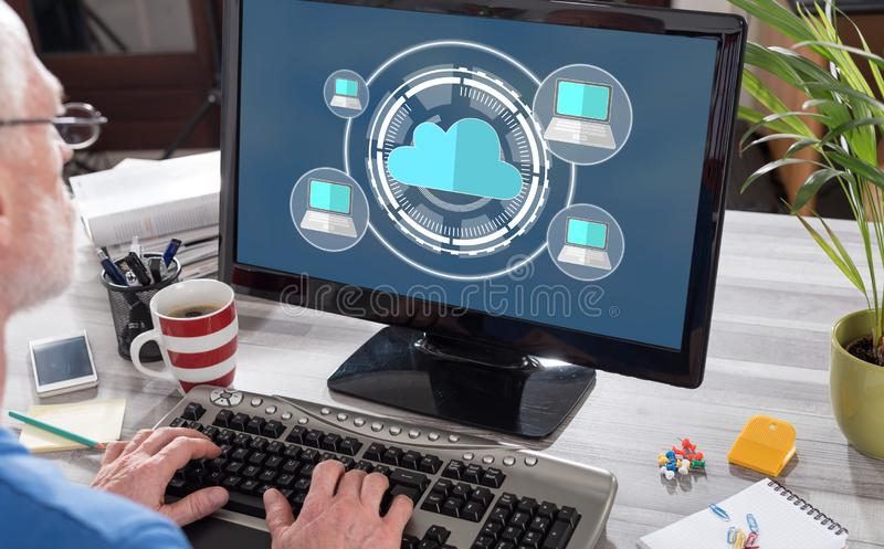 Cloud computing concept on a computer. Man using a computer with cloud computing concept on the screen royalty free stock photo
