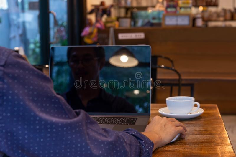 Man using computer mouse working on laptop at table in cafe. stock image
