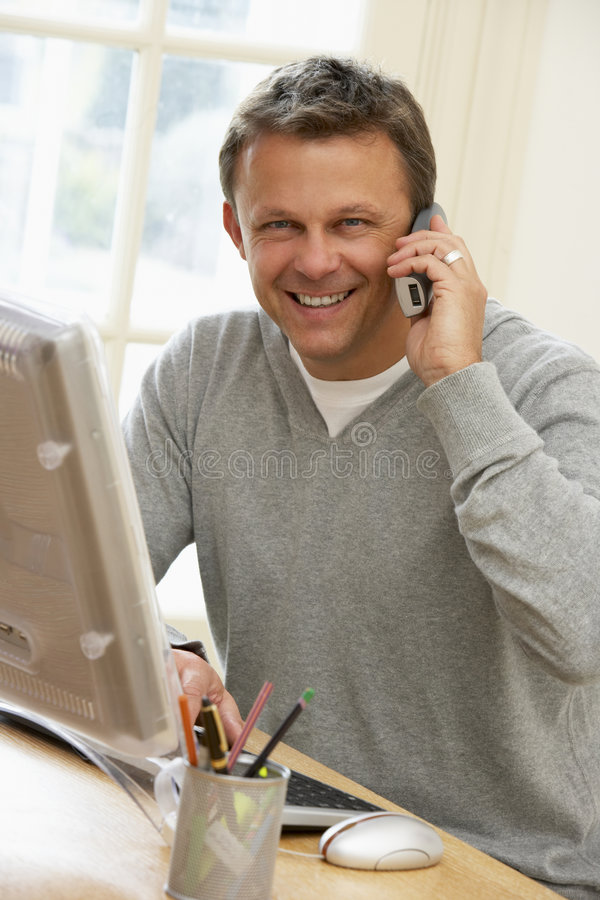 Man Using Computer And Talking On Phone stock images