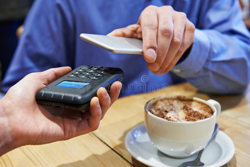 Man Using Contactless Payment App On Mobile Phone In Cafe. Man Uses Contactless Payment App On Mobile Phone In Cafe stock image