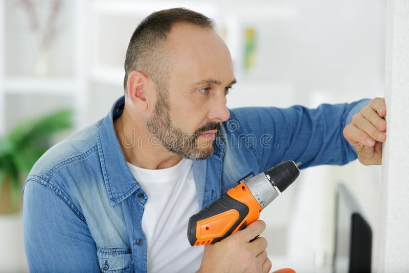 Man using cordless screwdriver in home. Man using cordless screwdriver in the home royalty free stock photo