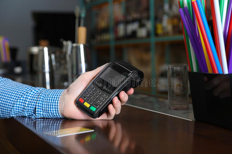 Man using credit card machine for non cash payment in cafe, closeup. Space for text royalty free stock image