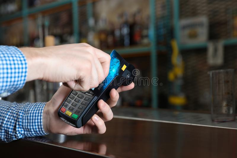 Man using credit card  for non cash payment in cafe, closeup. Space for text. Man using credit card machine for non cash payment in cafe, closeup. Space for text stock photography