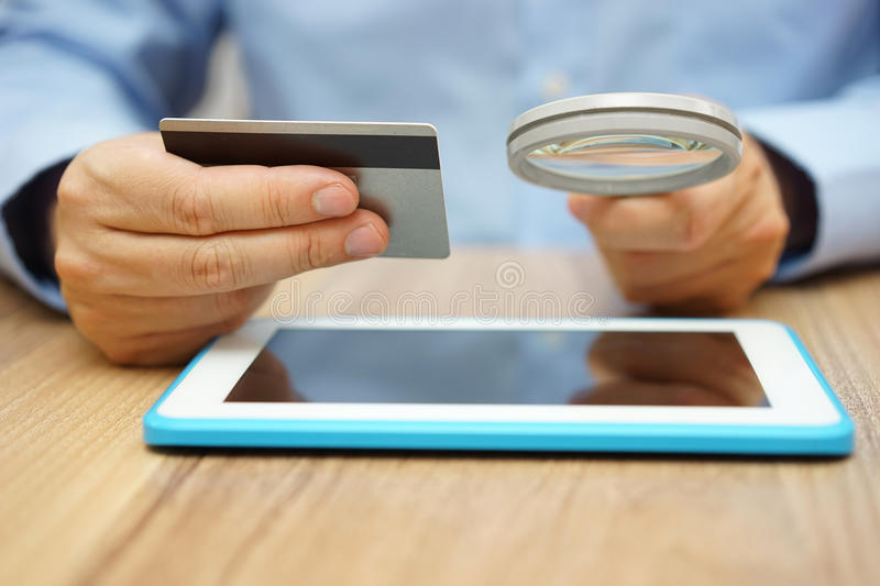 Man is using credit card for online payment. On tablet computer with magnifying glass stock photo
