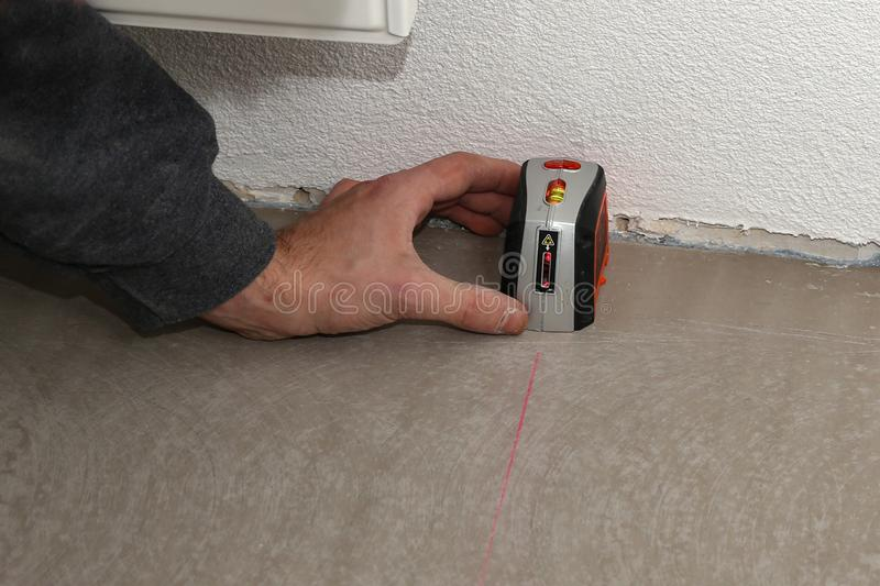 Man using cross-line laser to mark the floor stock photography