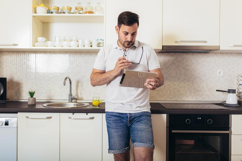 Man using digital tablet in kitchen at home stock photography