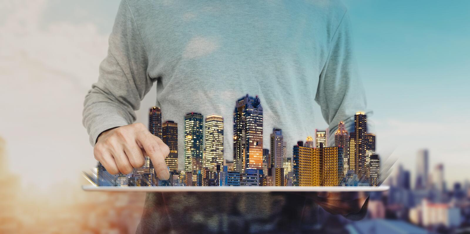 A man using digital tablet with modern buildings hologram. Real estate business and investment, building technology. A man using digital tablet with modern royalty free stock image
