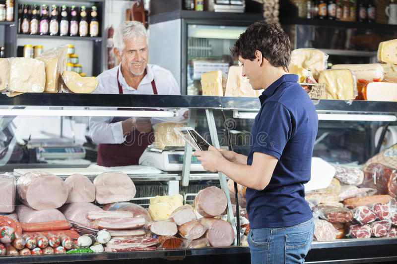 Man Using Digital Tablet While Salesman Packing Cheese royalty free stock photo