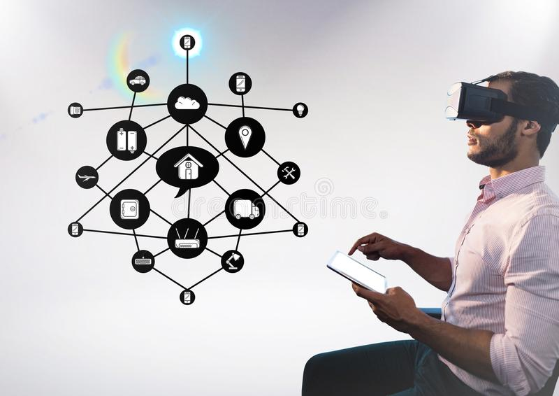 Man using digital tablet while wearing virtual reality headset with cloud connectivity interface stock image