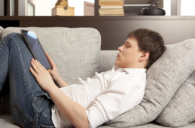 Man using a digital tablet. Young man using a digital tablet royalty free stock photography