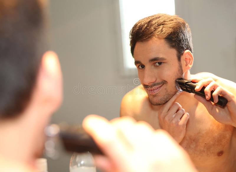 Man using electric razor and shaving in front of mirror. Man using electric shaver in bathroom royalty free stock images