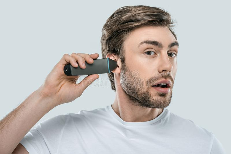 Handsome man using electric trimmer for ear. Isolated on grey stock photography