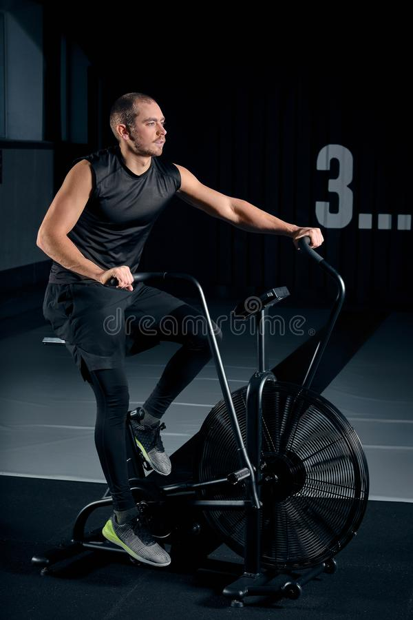Fitness male using air bike for cardio workout at Functional training gym. royalty free stock image