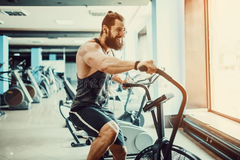 Young man using exercise bike at the gym. Fitness male using air bike for cardio workout at crossfit gym. royalty free stock photos