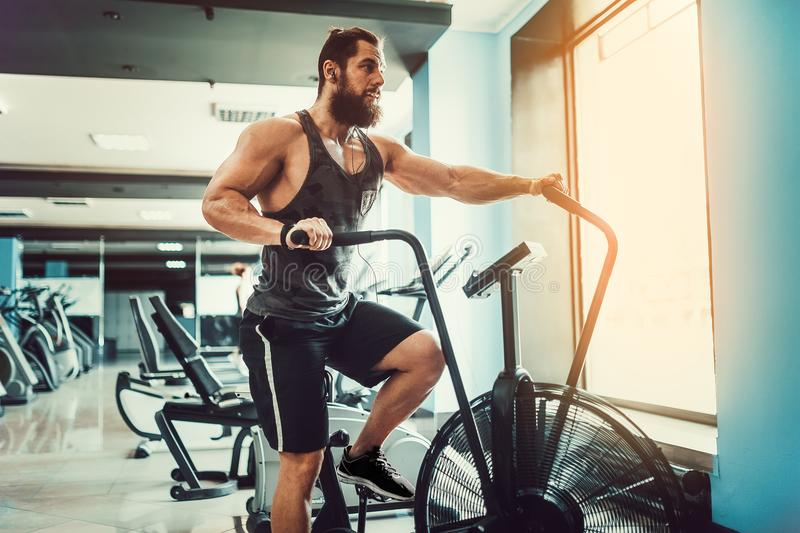 Young man using exercise bike at the gym. Fitness male using air bike for cardio workout at crossfit gym. stock images
