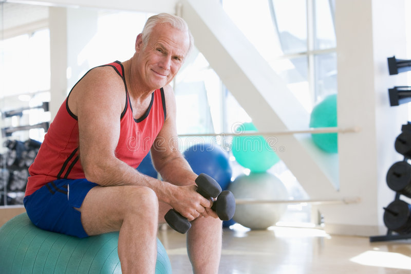 Download Man Using Hand Weights On Swiss Ball At Gym Stock Photo - Image: 7231104