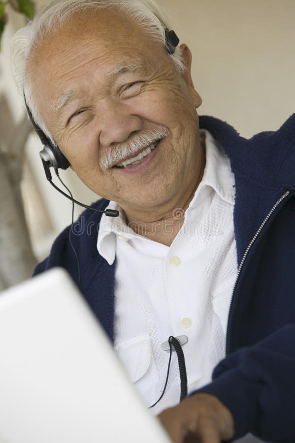 Man using headset and laptop smiling (portrait) royalty free stock images
