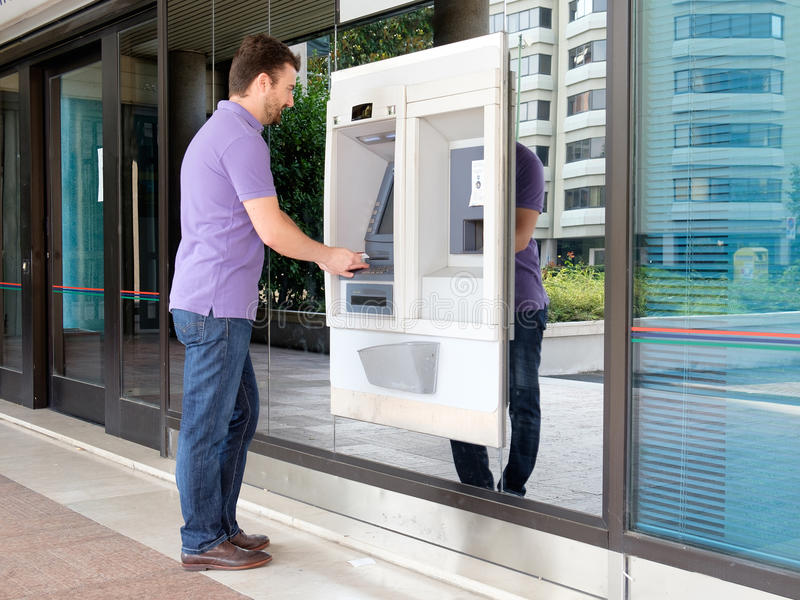 Man using his credit card in an atm for withdrawal. Man using his credit card in an atm for cash withdrawal stock photography