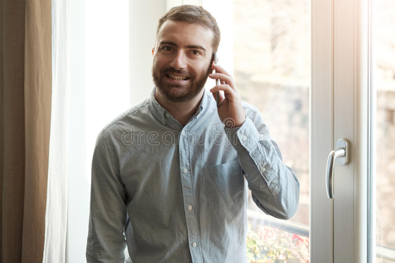 Man using his mobile phone at home royalty free stock image