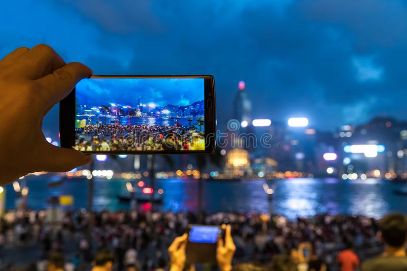 Man using his Mobile Phone to take photo of the crowed at seafront royalty free stock photos