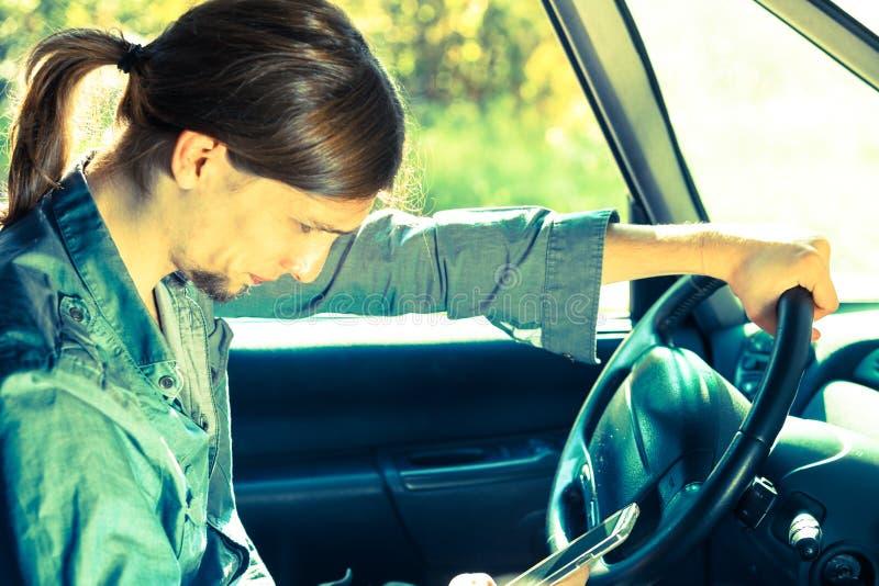 Man using his phone while driving car. Modern technology concept. Man using mobile phone while driving car, checking social media or setting navigation stock images