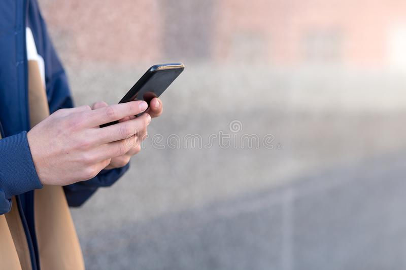 Man using his phone outdoors. Close up with copy space royalty free stock image