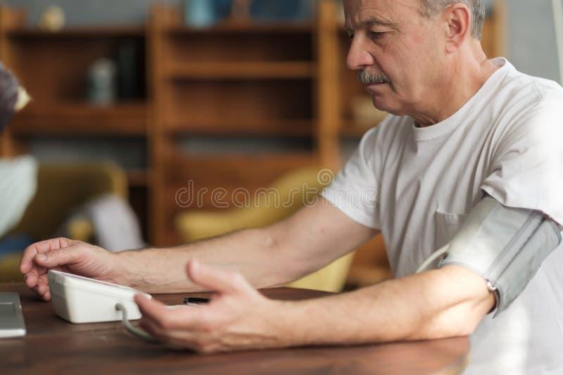 Man using home blood pressure machine to check his vital statistics. stock photo
